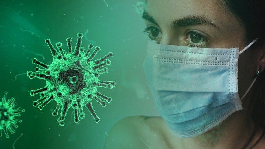 Frau mit Mundschutz neben einer Viruszelle