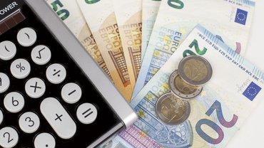 verschiedene Geldscheine und etwas Münzgeld liegen unter einem Taschenrechner